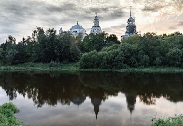 Вид на православный собор на берегу реки. пейзаж с видом на реку, деревья и отражение в воде в вечернем свете на закате. путешествовать
