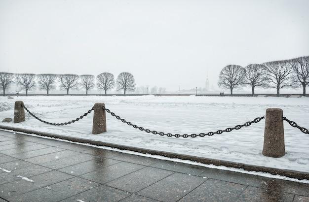 Вид на петропавловскую крепость и ряды деревьев сквозь сильный снегопад в санкт-петербурге.