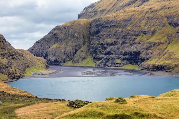 Вид на лагуну поллурин у села саксун. остров стреймой, фарерские острова