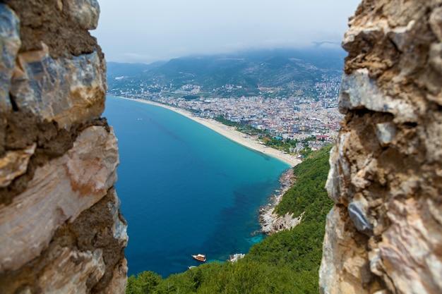 Вид на курортный город аланья, маяк в порту аланьи, старую крепость аланьи, турция.