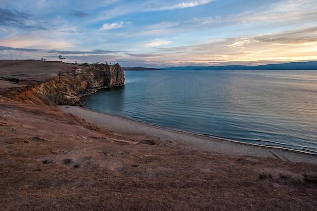 Вид на скалистый мыс и озеро байкал на острове ольхон на закате. голубая вода и небо с облаками. песчаный берег. пастельные тона.