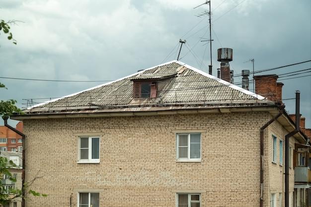 煙突とたくさんのテレビアンテナのある古いれんが造りの家の屋根の眺め