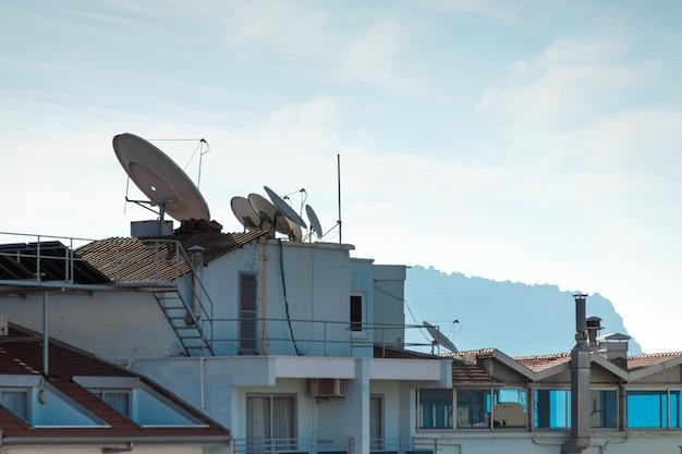 Вид на крыши домов с солнечными батареями и бочками с водой. концепция современные технологии, экономия электроэнергии.