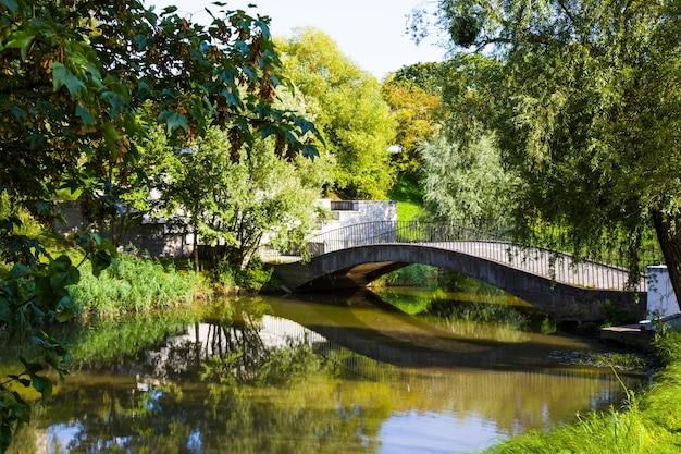 Вид на сцену небольшого моста через лесную речку в парке