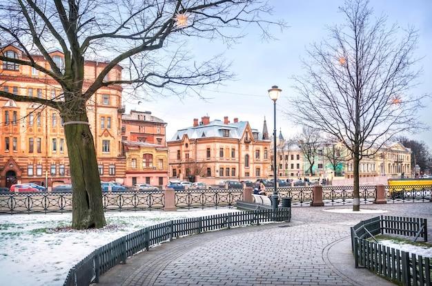 Вид на особняк шретера и другие дома на набережной мойки в санкт-петербурге с острова новая голландия в пасмурный зимний день