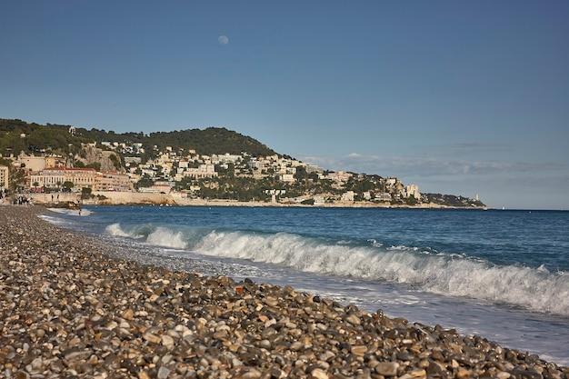 Вид на море и пляж ниццы с горами, простирающимися над морем