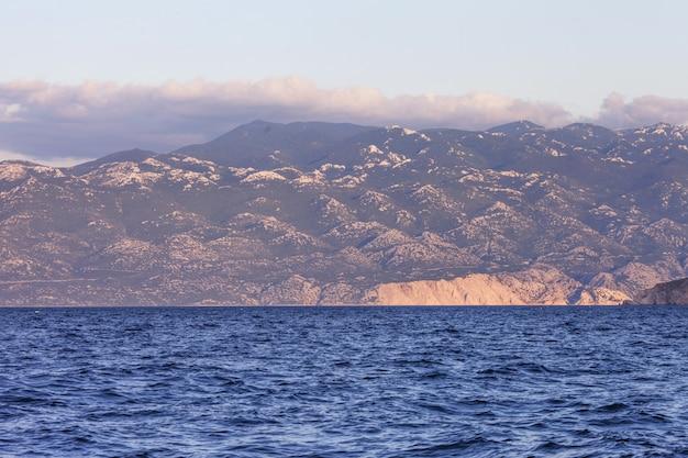 夕日または日の出の海と山の景色。景観の素晴らしさと静けさ