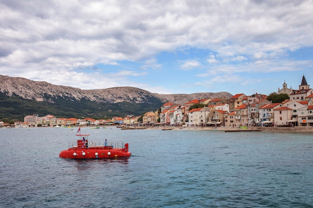 曇りの天候で海、山、船の景色。背景の家のある海岸。オレンジ色の屋根のある伝統的なクロアチアの町の風景。