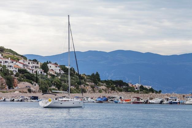 曇りの天候で海、山、船の景色。背景の家のある海岸