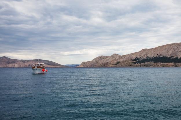 曇りの天候で海、山、船の景色。