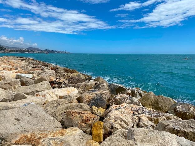 Вид на море, достигающее скал в малаге, средиземное море летом.
