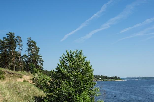 絵のように美しい川の岸と空の飛行機の痕跡の眺め