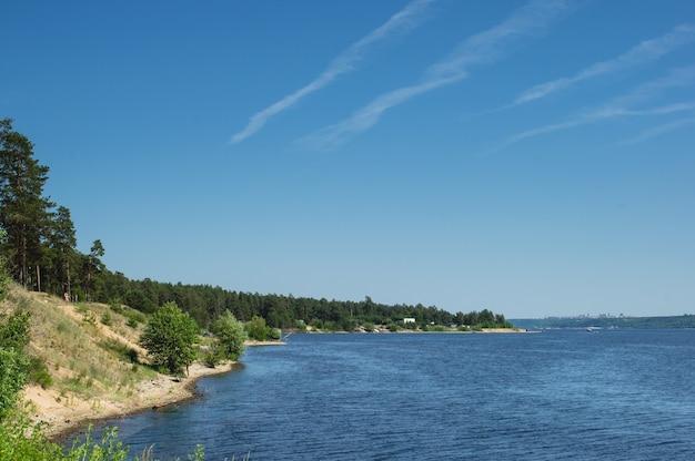 Вид на берег живописной реки и следы самолета в небе
