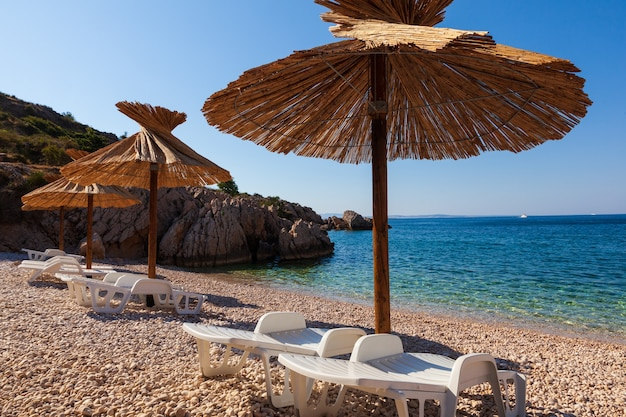 Вид на соломенные зонтики на красивом пляже опрна в адриатическом заливе острова крк, в хорватии