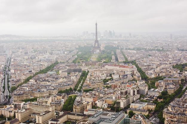 Вид на улицы парижа с высоты. путешествие по европе. достопримечательности во франции. облачный париж. облака в небе. эйфелева башня