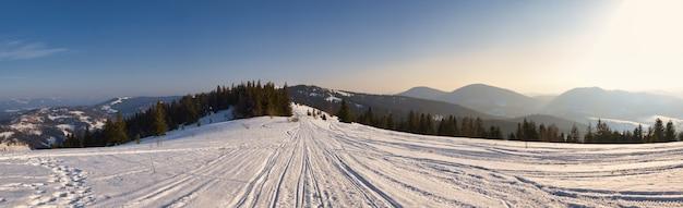 緑豊かな白い雲に囲まれた雪の斜面と丘の見事な冬のパノラマの眺め。厳しい冬の自然を魅了するコンセプト