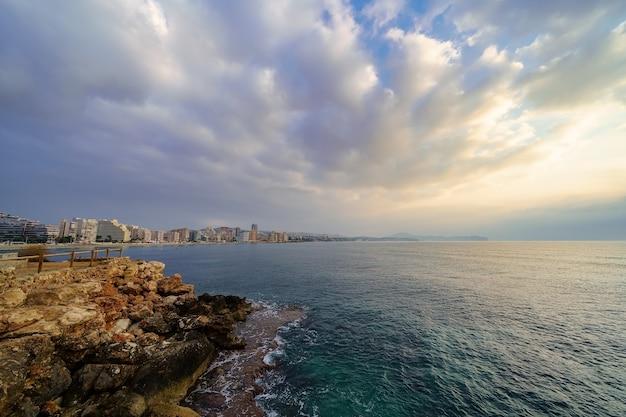 見事な雲と黄金の夕日の海のそばの夏の街の眺め。