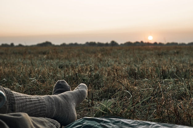 テント、足、毛布、日の出からの日の出の眺めが見えます。旅行、自然の中で日の出に会う。