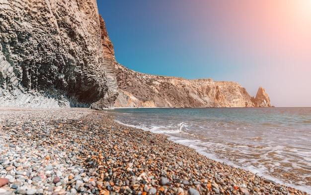 Вид на закатное море и пляж вулканическая скала освещена теплым закатным песком и галькой.