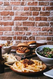 木製のテーブルにさまざまな料理、ハンバーガー、フライドポテト、サラダ、ドリンク、ソースが付いたテーブルの眺め。レストランのメニュー。縦画像