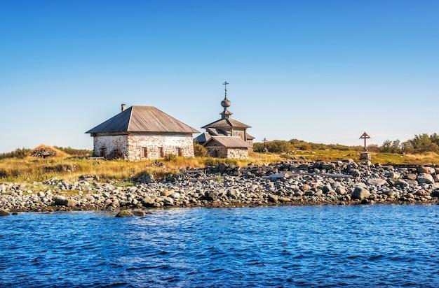 Вид на храм и каменные дома на заяцких островах и побережье белого моря в лучах осеннего солнца