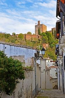 グラナダの狭い通りからのアルハンブラ宮殿のランプの塔の眺め