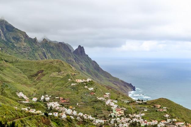 テネリフェ島北部のタガナナの町の眺め。海の海岸に多くの小さな白い家がある山の緑の風景。