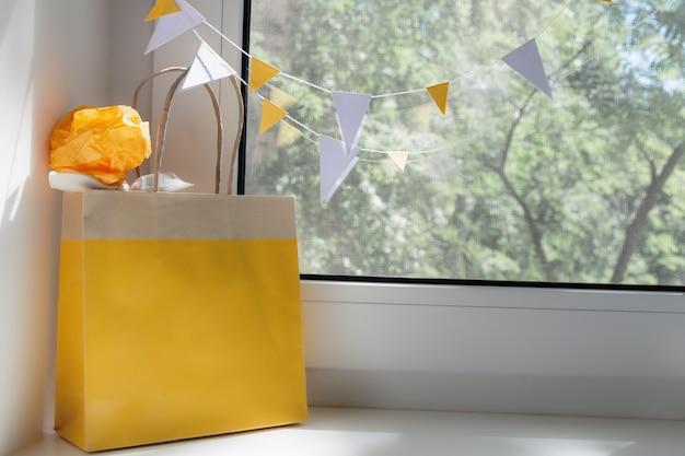 窓に贈り物が付いている黄色いバッグのビュー。休日の概念、背景。