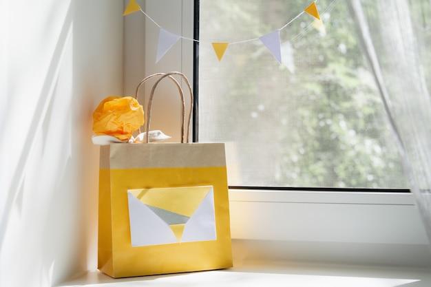 窓に贈り物が付いている黄色いバッグのビュー。休日の概念、背景。 Premium写真
