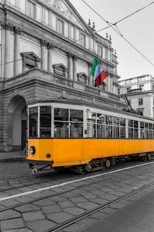 Вид на желтый трамвай, проезжающий перед театром в милане, италия