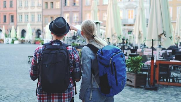 Взгляд пары туристов с сумками, проверяющими карту на центральной площади города. они обсуждают свое новое место назначения.