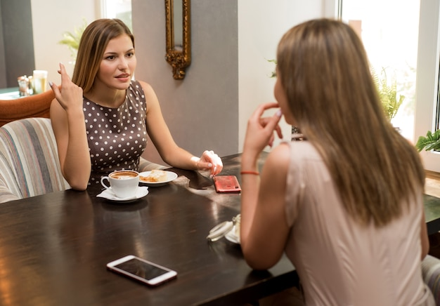 Вид двух молодых красивых женщин, сидящих друг напротив друга за столом в ресторане во время обеда