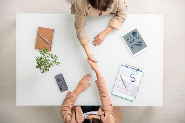Вид двух молодых успешных деловых женщин, обменивающихся рукопожатием над столом после заключения сделки между финансовой информацией на планшете и на бумаге
