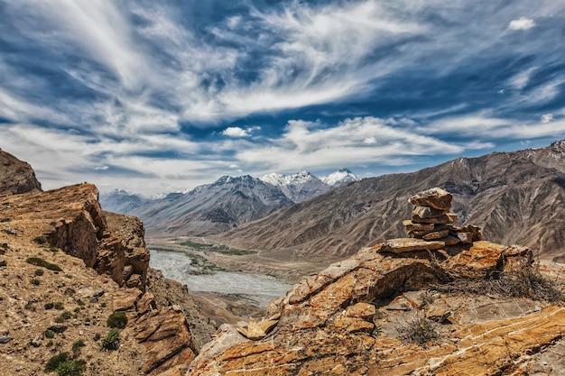 Вид на долину в гималаях с каменной пирамидой из камней на скале