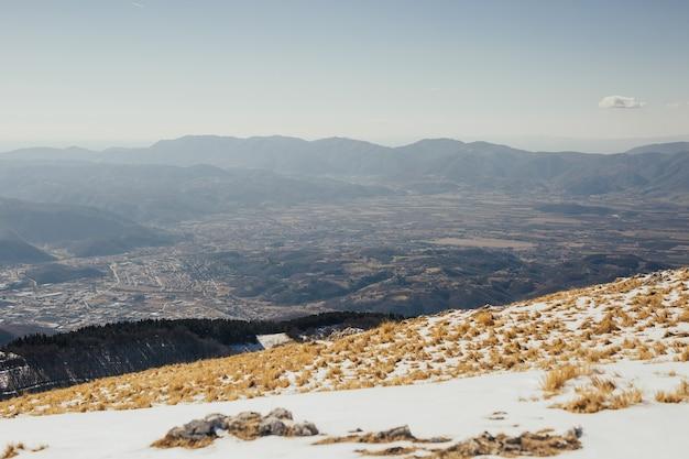 흩어져있는 집들이있는 마을의 전망. 눈 덮인 산에서 봅니다.