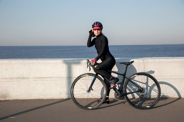 ウォーターフロントの女性アスリートサイクリストのビュー