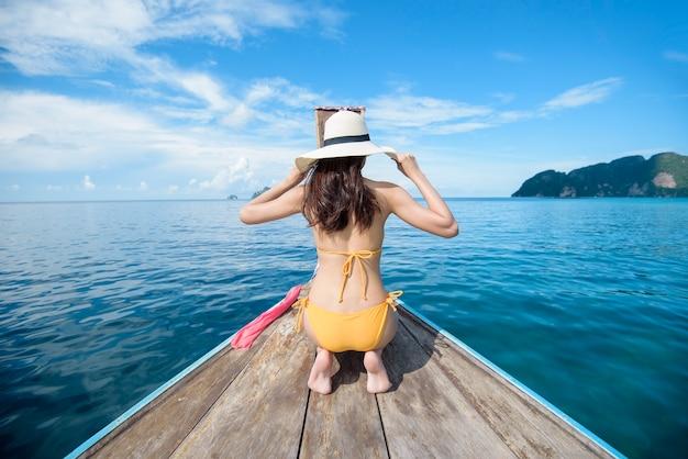 Вид женщины в купальнике, наслаждающейся на тайской традиционной длиннохвостой лодке над красивыми горами и океаном, острова пхи-пхи, таиланд