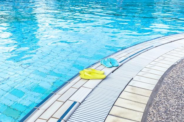 プールのそばのボートの上に立っている黄色と青のサンダルの眺め。夏、休暇、スパ、ウォーターパーク、旅行の概念