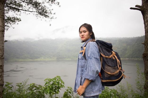 Вид молодой азиатской женщины, стоящей перед лесом озера