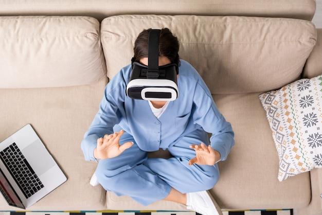 Вид молодой брюнетки-бизнес-леди в домашней одежде и гарнитуре vr, касающейся виртуального дисплея, сидя на диване и готовя презентацию