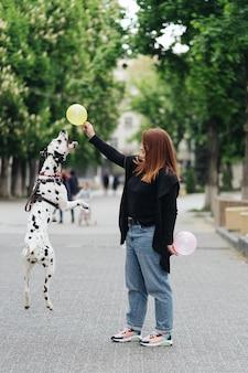 Вид молодой кавказской женщины, играющей и дрессирующей свою далматинскую собаку, плюс размер самки, проводящей досуг с лучшим другом домашнего животного, наслаждаясь выходными на улице