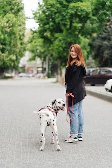 ダルメシアン犬と一緒に朝の時間の間に街を歩いている若い白人女性のビュー