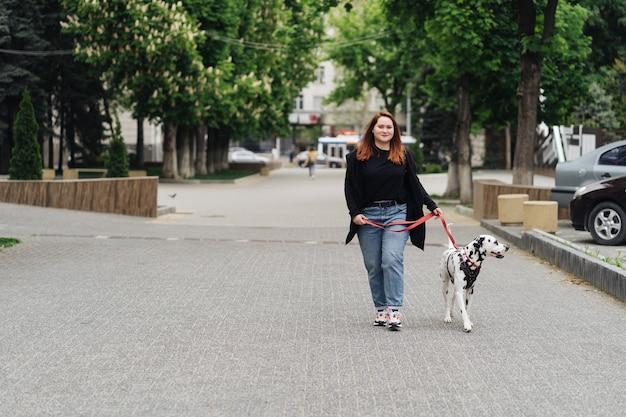 Вид молодой кавказской женщины, прогулки по городу в утреннее время с далматинской собакой