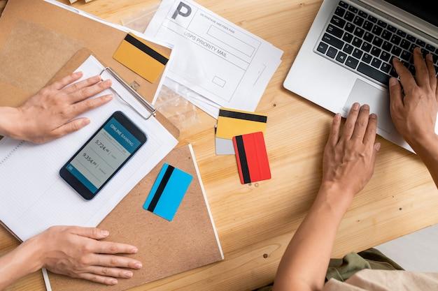 Взгляд молодых женщин-менеджеров передает рабочее место во время проверки информации об онлайн-заказах клиентов и предоплате