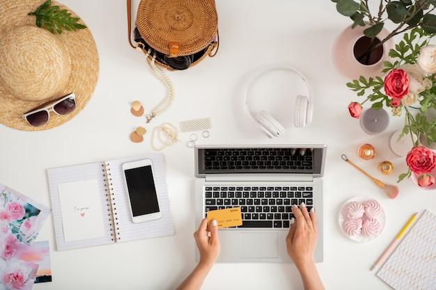 Вид на руки молодой женщины-покупателя с пластиковой картой, вводящей личную информацию во время покупок в интернете перед ноутбуком