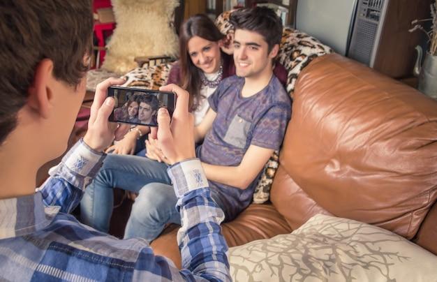 ソファに座っている流行に敏感な10代のカップルにスマートフォンで写真を撮る若い友人のビュー。電話の画面に焦点を当てます。
