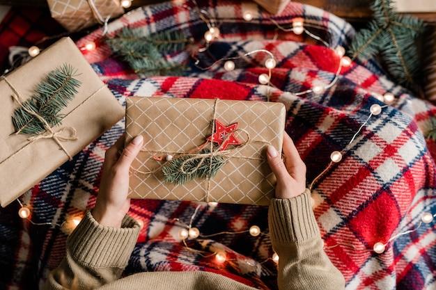 Вид молодой женщины, завернутой в теплый клетчатый плед, держащей подарочную коробку с украшением из хвойных деревьев и красной звездой наверху