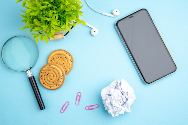 Above view of office concept with headphone mobile phone flower cookies crushed paper magnifying glass on blue surface