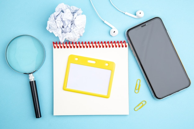 Above view of office concept with headphone mobile phone spiral notebook crushed paper magnifying glass on blue surface