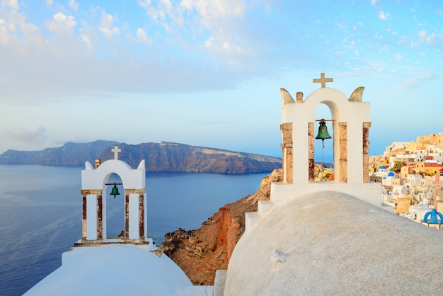 View on oia village on santorini island over church bell towers